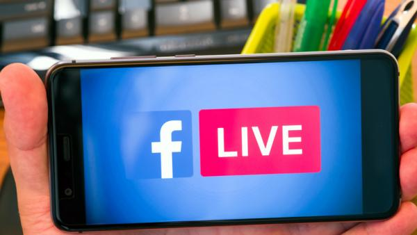 Hand holding mobile phone with Facebook Live on screen