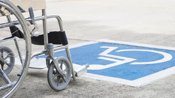 wheelchair by disabled sign on ground