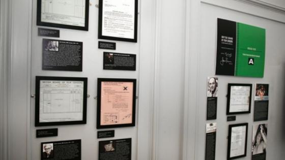 In the image there are different frames of images and certificates hung a wall