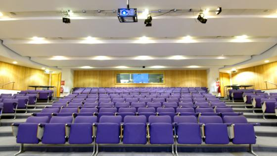 A large lecture theatre with purple seats and a tech box towards the back of the room