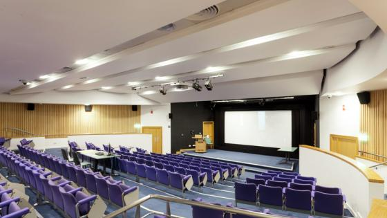 A large lecture theatre with purple seats, a large screen and a stage with a podium