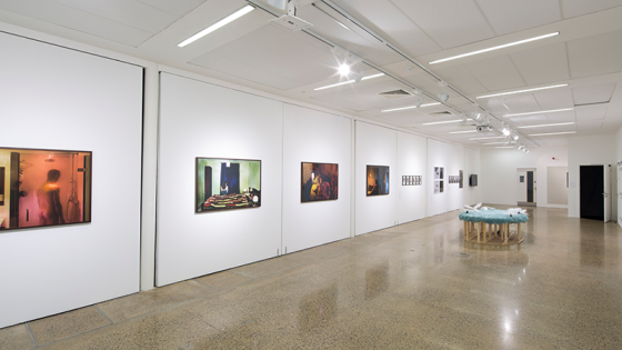 A large white room with artwork hanging on the walls