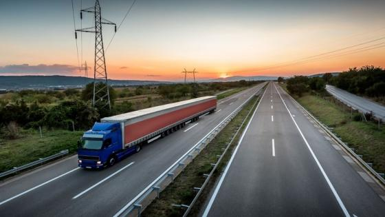 A truck driving on the motorway with  the sunset in the bakground