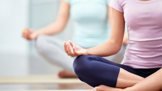 Two ladies sitting crossed legged doing yoga