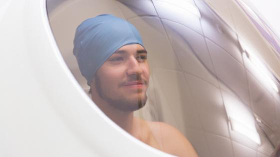 An athlete sitting in the BodPod chamber - a pod with a glass window. The athlete is smiling.