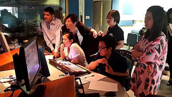Participants in a media editing room looking at a screen