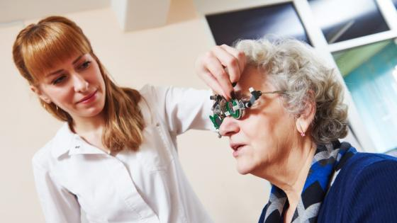An optometrist helping a patient
