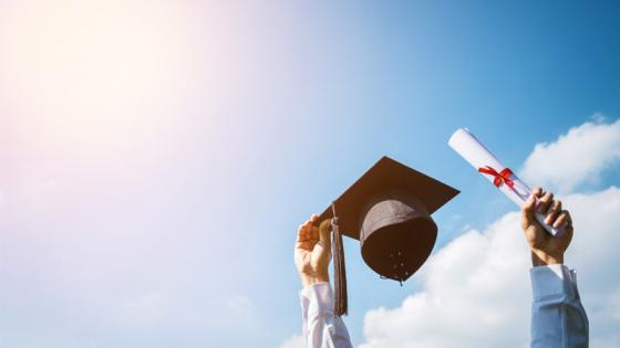 Person holding up a graduation cap and scroll in each hand on a sky background