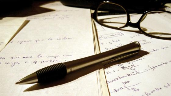 Pen and glasses placed on written pieces of paper