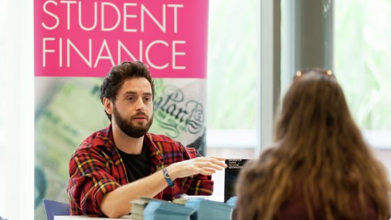 University of Westminster, Cavendish Campus Open Day 2014: a female student (back turned) talks to a male staff member at an information desk with a banner reading Student Finance