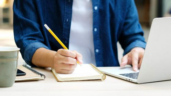 Student taking notes during an online event feature