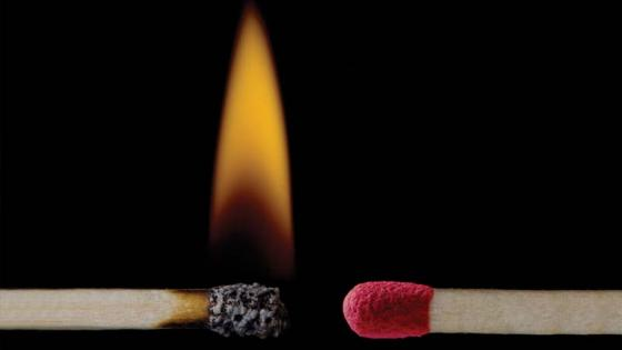Two matchsticks, one is burning, the other unlit