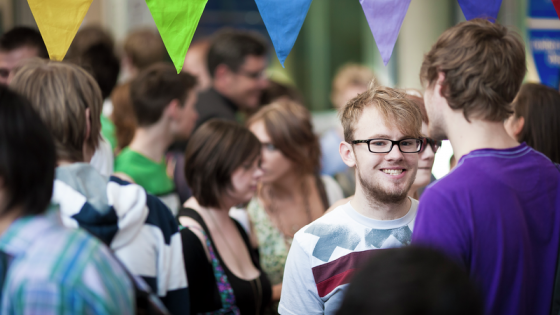 male student smiling at camera, surrounded by other students, and colourful bunting above him.